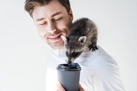 Photo pour Homme souriant avec le raton laveur mignon potable de tasse jetable sur le gris - image libre de droit