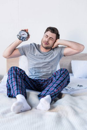 Photo for Handsome man stretching and holding alarm clock while sitting on bedding - Royalty Free Image