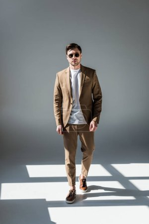 Photo for Good-looking stylish man in beige suite and sunglasses standing in sunlight on grey - Royalty Free Image