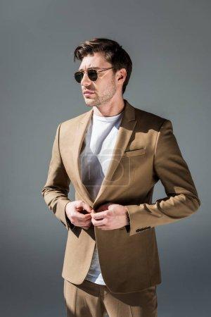 Photo pour Homme élégant sérieux dans la suite beige et les lunettes de soleil regardant loin sur le gris - image libre de droit