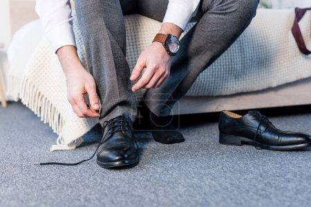 Photo for Partial view of man putting on black leather shoes while sitting on bedding - Royalty Free Image