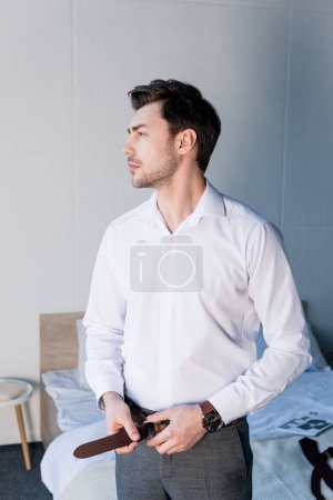 Photo for Confident handsome man dressing in bedroom and looking away - Royalty Free Image
