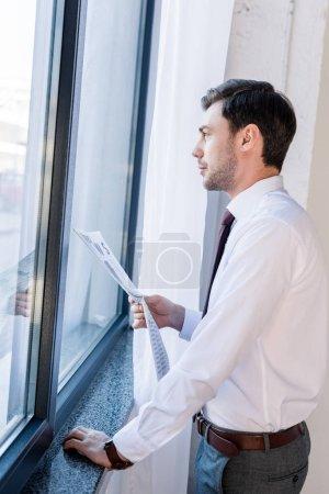 Photo pour Homme confiant de bonne qualité restant par la fenêtre avec le journal et regardant loin - image libre de droit