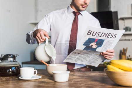Photo for Cropped view of man reading business newspaper while standing by kitchen table and pouring milk into bowl - Royalty Free Image