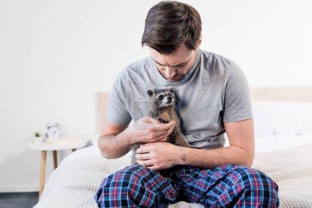 Foto de Hombre guapo en pijama sentado en la cama y abrazando con mapache divertido - Imagen libre de derechos