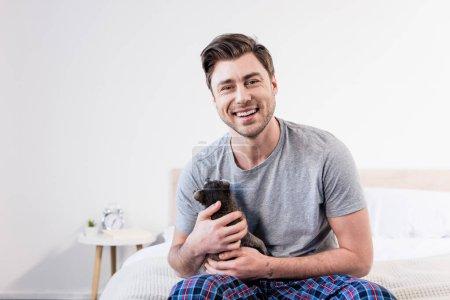 Foto de Hombre alegre en pijama sentado en la ropa de cama y abrazos con mapache lindo - Imagen libre de derechos