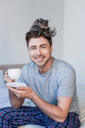 Foto de Hombre alegre con mapache divertido en la cabeza sosteniendo la taza de café y mirando a la cámara - Imagen libre de derechos