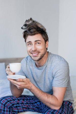 Foto de Hombre alegre con mapache divertido en la cabeza sosteniendo taza de café mientras está sentado en la ropa de cama - Imagen libre de derechos