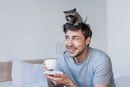 Foto de Alegre guapo hombre con lindo mapache en la cabeza sosteniendo taza de café mientras está sentado en la ropa de cama - Imagen libre de derechos