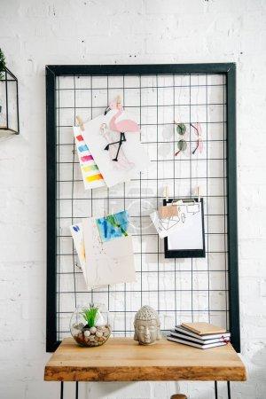 Photo pour Pinboard avec des dessins et des verres et une table en bois dans la chambre d'adolescent - image libre de droit