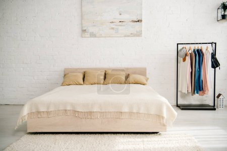 Photo for Light bedroom with big bed, carpet and straight rack - Royalty Free Image