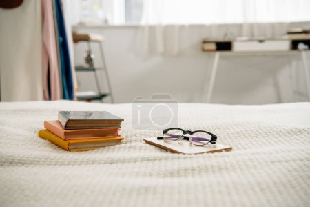 Photo for Books and glasses on bed in light cozy bedroom - Royalty Free Image