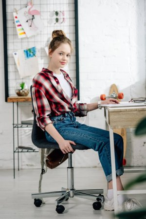 Photo for Cute teenage kid in jeans sitting on chair at table and looking at camera - Royalty Free Image