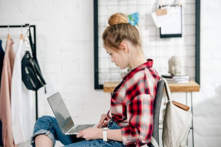 Photo for Teenage kid in red checkered shirt using laptop at home - Royalty Free Image
