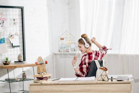 Photo for Joyful teenage kid in red checkered shirt listening music in headphones - Royalty Free Image