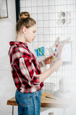 Photo for Side view of pensive teenager in checkered shirt looking at drawing - Royalty Free Image