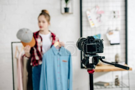 Photo for Selective focus of teenager holding cap and shirt in front of video camera - Royalty Free Image