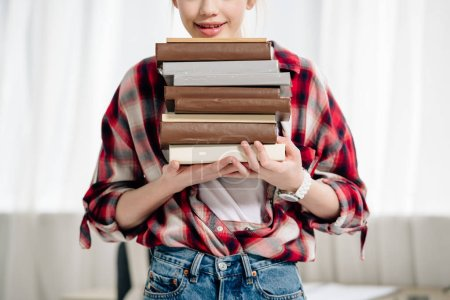 Photo for Cropped view of teenage kid in red checkered shirt holding books at home - Royalty Free Image