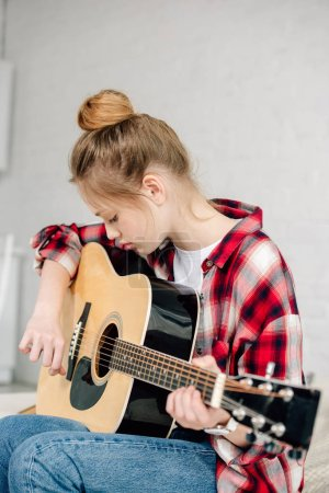 Photo for Concentrated teenager in checkered shirt playing acoustic guitar at home - Royalty Free Image