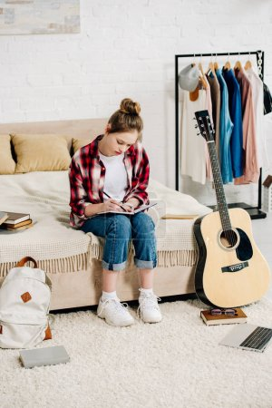 Photo for Concentrated teenager with notebook sitting on bed and doing homework - Royalty Free Image