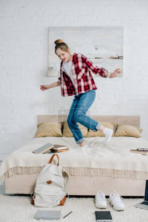 Photo for Full length view of smiling teenager kid in jeans jumping on bed at home - Royalty Free Image