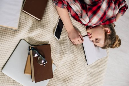 Photo for Teenager in checkered shirt sleeping on bed with books and smartphone - Royalty Free Image