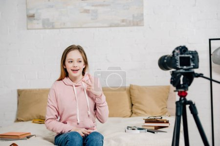 Photo for Joyful teenage blogger showing peace sign at video camera - Royalty Free Image