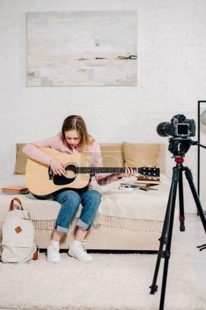 Foto de Blogger adolescente sentado en la cama y tocando la guitarra acústica delante de la cámara - Imagen libre de derechos