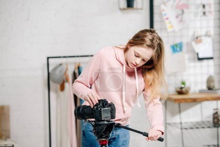 Photo for Teenage blogger in pink hoodie setting up video camera at home - Royalty Free Image