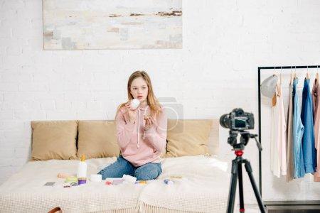 Photo pour Adolescent blogueur s'asseyant sur le bâti et montrant des produits de beauté à l'appareil-photo - image libre de droit