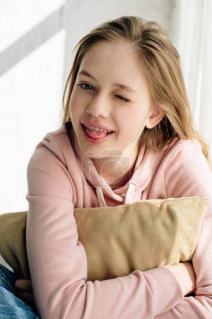 Photo pour Enfant adolescent souriant embrassant le coussin brun et regardant l'appareil-photo - image libre de droit