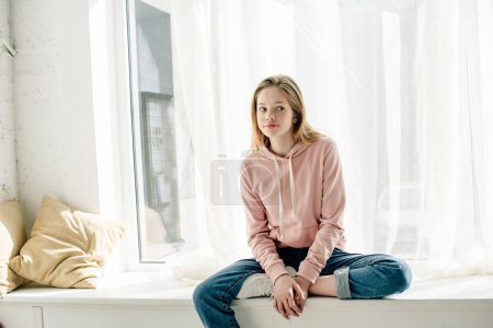 Photo for Pensive teenage kid in jeans sitting on window sill and looking away - Royalty Free Image