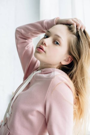 Photo for Teenage kid in pink hoodie touching hair and looking at camera - Royalty Free Image