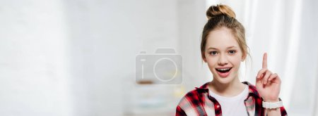 Photo for Panoramic shot of smiling teenager in checkered shirt showing idea sign - Royalty Free Image