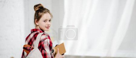 Photo pour Plan panoramique de l'adolescence avec le sac à dos retenant des livres et regardant l'appareil-photo - image libre de droit