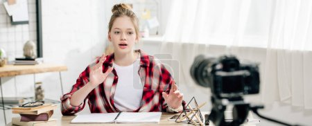 Photo for Panoramic shot of teenage blogger in checkered shirt sitting at table in front of video camera - Royalty Free Image