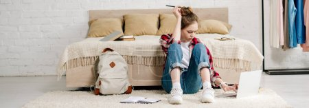 Photo for Teenager with laptop sitting on carpet and doing homework - Royalty Free Image