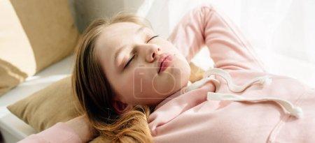 Photo pour Plan panoramique de gosse d'adolescent dormant sur le coussin brun - image libre de droit