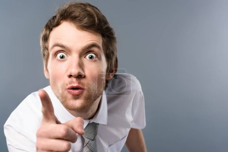 aggressive businessman with funny face expression pointing with finger at camera