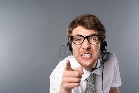 Irritierter Call-Center-Betreiber mit Headset und Brille zeigt mit Finger auf Kamera