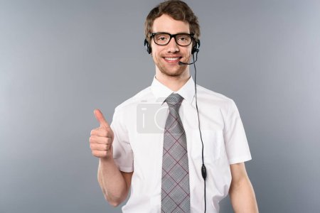 smiling call center operator in glasses and headset showing thumb up on grey background