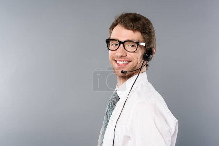 smiling call center operator in headset and glasses looking at camera