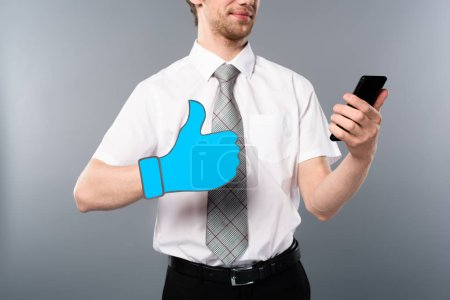 Photo for Cropped view of businessman in glasses with paper cut thumb up using smartphone on grey background - Royalty Free Image