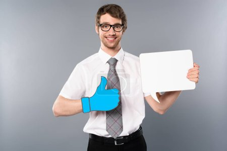 Photo for Positive businessman in glasses with paper cut thumb up holding white empty card on grey background - Royalty Free Image