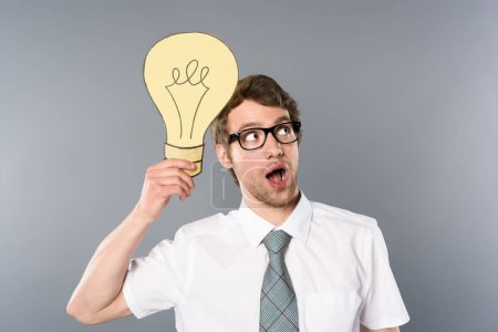 Photo for Dreamy businessman in glasses holding yellow paper cut light bulb on grey background - Royalty Free Image