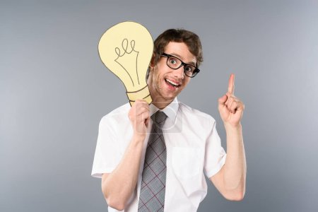 Photo for Smiling businessman in glasses holding yellow paper cut light bulb and showing idea gesture on grey background - Royalty Free Image
