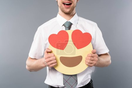 Photo for Cropped view of excited businessman holding smiling face with heart-eyes - Royalty Free Image