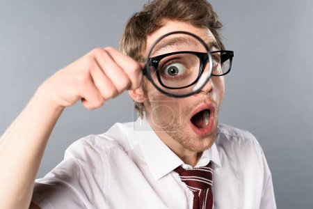 Photo for Shocked businessman in glasses with funny face expression looking in magnifier on grey background - Royalty Free Image