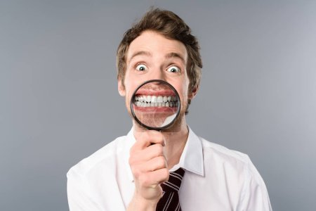 Photo for Smiling businessman with funny face expression holding magnifier on grey background - Royalty Free Image