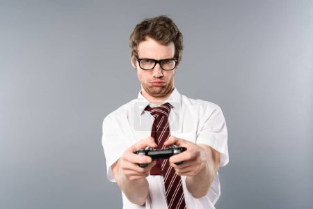 Photo for Upset businessman playing video game with joystick on grey background - Royalty Free Image
